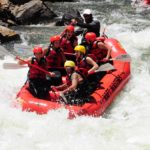Raft with people in it navigating through rapids on Clear Creek